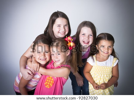 Fun portrait of five smiling happy little girls - stock photo