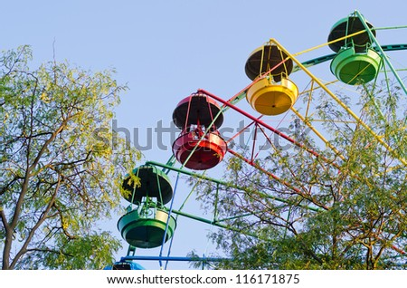 Fun ride at a fairground with a partial view of a small multicoloured ferris wheel with colourful gondolas midair - stock photo