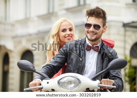 Fun ride. Beautiful young couple riding scooter together while happy woman bonding to her boyfriend and smiling - stock photo