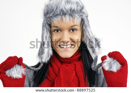 Fun smiling friendly young woman ready for the cold weather with her furry grey hat and red scarf and mittens. - stock photo