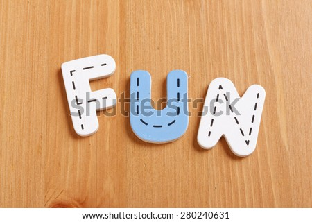 FUN, spell by woody puzzle letters with woody background - stock photo