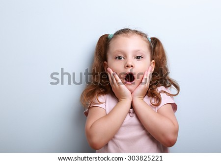Fun surprising kid girl with opened mouth looking on blue background with empty copy space - stock photo