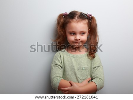 Fun thinking kid girl looking on blue wall background. Closeup portrait - stock photo