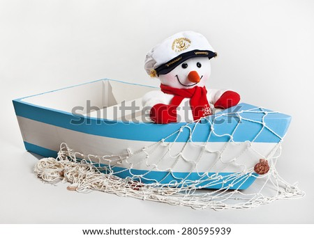 Fun toy snowman in a wooden boat with a fishing net on a white background - stock photo