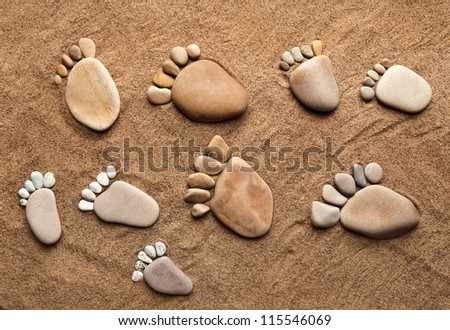 fun trace bare feet walking, made of pebble stones on the top view surface beach sand background - stock photo