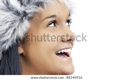Fun winter time theme: close up of a friendly beautiful young woman wearing grey faux fur hat, profile portrait looking up smiling and laughing. - stock photo