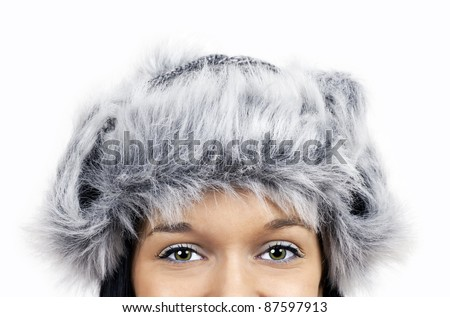 Fun winter time theme: close up on the green eyes of a smiling friendly beautiful young woman wearing grey faux fur hat. - stock photo