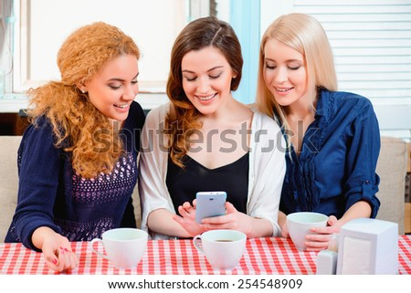 Fun with best friends. Three young beautiful female friends sitting in cafe and talking  - stock photo