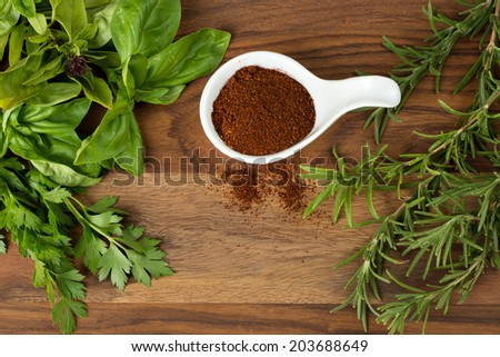 Fun with food, fresh basil and parsley,on the left, fresh rosemary on the right. White porcelain bowl filled with chili powder dead center. This is shot on a wood table. - stock photo