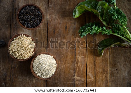 Fun with food, small wood bowls filled with brown rice, quinoa and wild rice on the left, kale and Swiss chard on the right. Copy space dead center. This is shot on a wood table. - stock photo