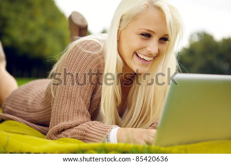 Fun with laptop in park - stock photo