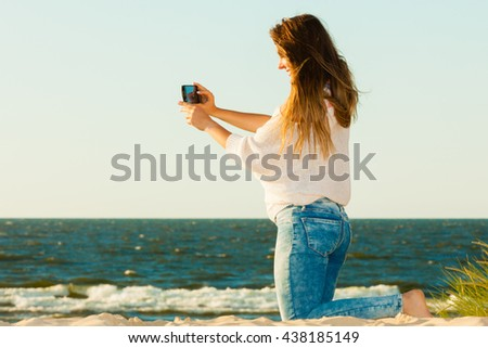 Fun with photography. Young smiling woman with mobile phone taking selfie picture photo. Happy cute gril with long hair blowing on wind.