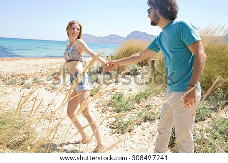 Fun young tourist couple with woman taking man hand and pulling, running towards the sea, enjoying a summer holiday together on a beach exterior. Travel lifestyle romantic vacation, nature exterior. - stock photo
