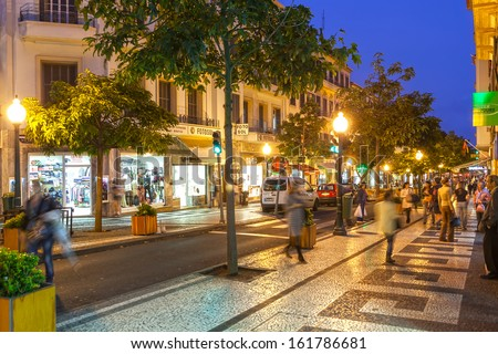 FUNCHAL, MADEIRA/PORTUGAL- NOVEMBER 2: Streets of the historical city center with shops and people walking at night shown on 2 November 2011 in Funchal, Madeira, Portugal.  - stock photo