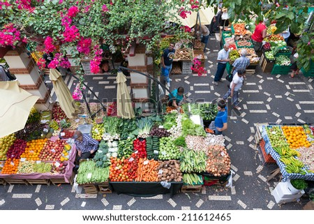 FUNCHAL, PORTUGAL - AUG 01: People are shopping at the vegetable market of the famous Mercado dos Lavradores on August 01, 2014 in Funchal, capital city of Madeira, Portugal - stock photo