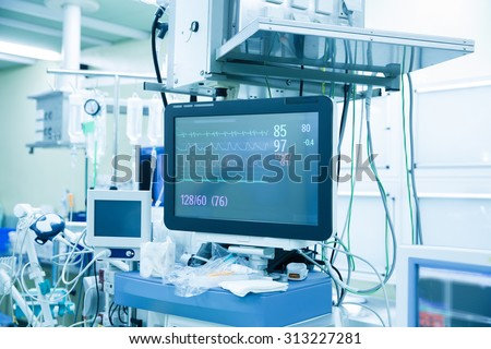 Functional vital functions (vital signs) monitor in an operating room with machines in the background, during real surgery on a patient. Life sustainment, monitoring and anesthesia concept.  - stock photo