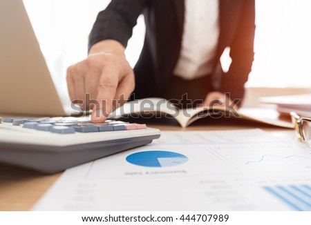 Fund manager use a calculator to calculate return on investment. - stock photo