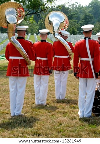 Funeral at Arlington National Cemetery with with military band in foreground and gravestones in background - stock photo