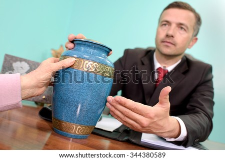 funeral director showing urn - stock photo