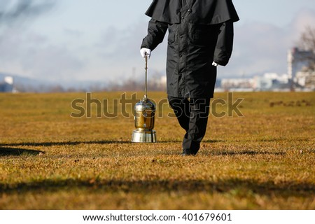 Funeral director, undertaker, carrying an extravagant urn with ashes of a cremated human during a formal scattering ceremony. Death, cremation, funeral, Day of the dead concept. 