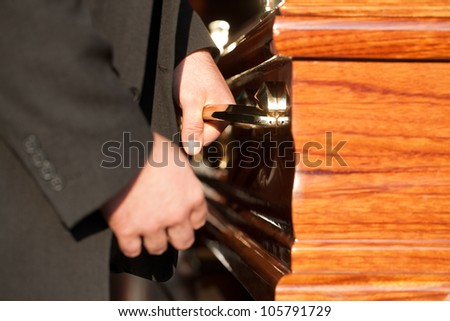 Funeral with coffin on a cemetery, the casket carried by coffin bearer - stock photo