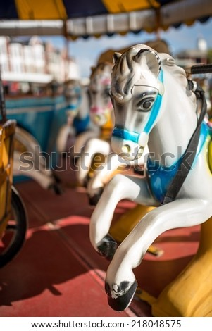 Funfair horses on merry go round or carousel at a british seaside town. - stock photo