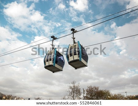 Funicular - one of the popular Istanbul urban transport. Modular cabins cable car against the bright sky and clouds.