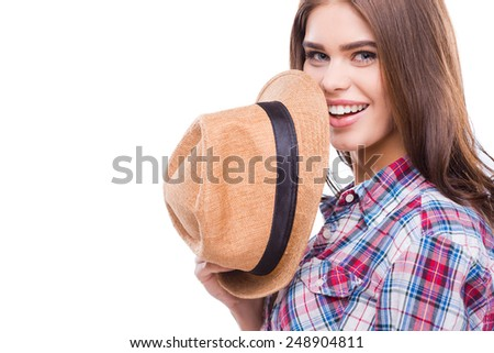 Funky beauty. Beautiful young woman in funky wear holding hat and smiling while standing against white background - stock photo