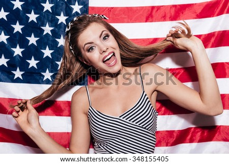 Funky beauty. Cheerful young woman touching her hair and smiling while standing against American national flag - stock photo