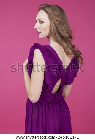 Funky fresh and playful girl. Beautifull young girl, blonde hair on pink background and in violet dress - stock photo