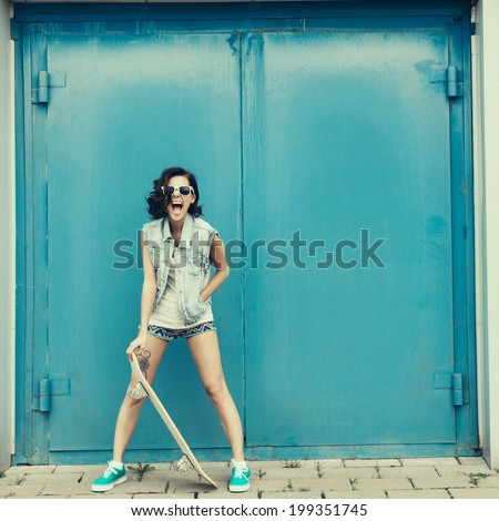 Funky girl posing with skateboard. Lifestyle outdoor portrait - stock photo