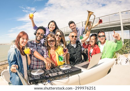 Funky hipster people taking selfie and having fun together at beach rave afterhour party - Summer festival moments with young disc jockey happy friends - Dj playing trendy sound at open air disco club - stock photo