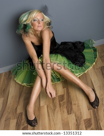 Funky looking young woman sitting in black and green prom dress.