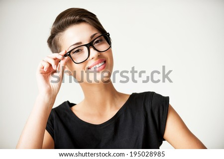 Funky style beauty. Beautiful young short hair woman adjusting her glasses and smiling - stock photo