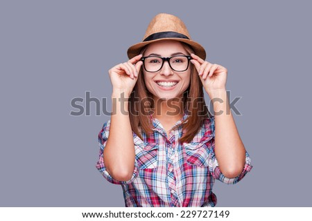Funky style beauty. Portrait of beautiful young woman in glasses and funky hat adjusting her glasses and smiling while standing against grey background - stock photo