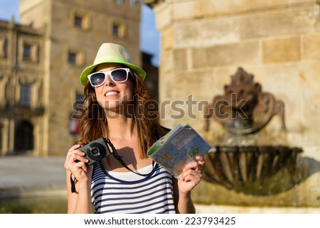 Funky woman on summer vacation travel visiting typical spanish landmark in Asturias. Female tourist taking photos in Plaza Marques and Revillagigedo Palace , Gijon, Spain. - stock photo