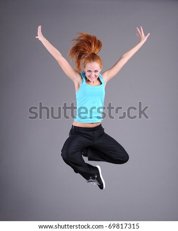 funky young woman jumping and dancing isolated on grey background