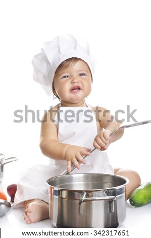 Funny adorable baby boy chef sitting and playing with kitchen equipment on a white background - stock photo