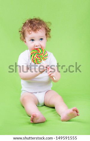 Funny adorable baby with a big candy on green background - stock photo