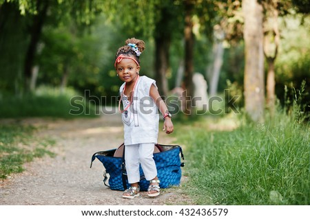Funny african baby girl with big bag at park - stock photo