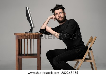 Funny and crazy man using a computer on gray background. man's hand pointing at the monitor. Concept of surprise and indignation - stock photo