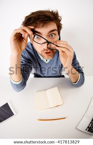 Funny and crazy tired handsome young businessman in glasses sitting at the office desk on white background. Looking at camera. Wide angle.