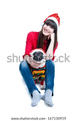 Funny and cute friends a pretty girl and her pug dog pet wearing red Santa Claus caps, having fun, smiling with toothy smiles, dog being serious, both looking at camera. Isolated on white background - stock photo