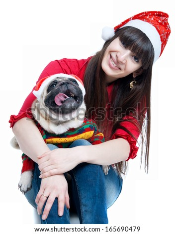 Funny and cute friends pretty girl and her pug dog pet wearing red Santa Claus caps, having fun, smiling with toothy smiles, dog showing tongue looking at camera. Isolated on white, main focus on girl - stock photo
