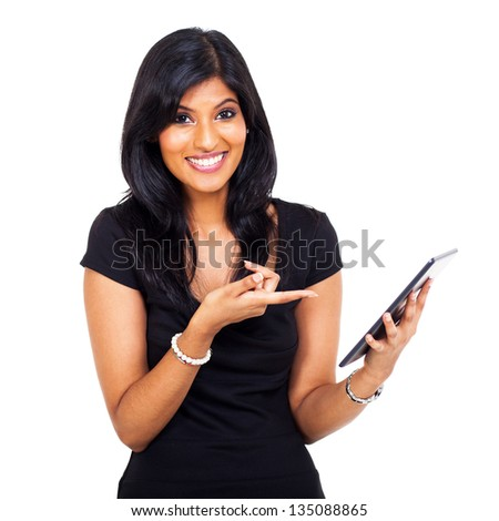 funny and cute young indian woman pointing tablet computer on white background - stock photo