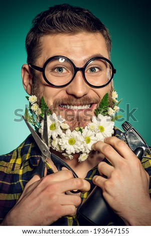 Funny and handsome young man cut his beard of flowers with scissors.  - stock photo