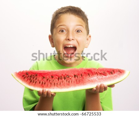 Funny and happy little boy eating watermelon.Little boy holding a big watermelon. - stock photo