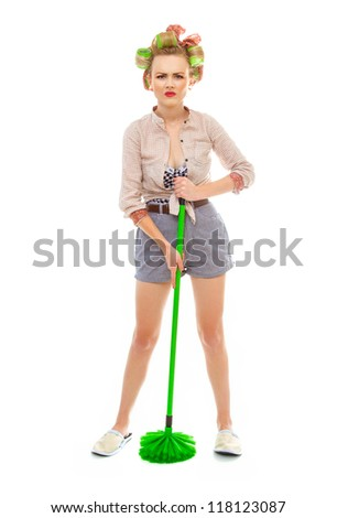 Funny angry or unhappy housewife / girl with broom, isolated on white. Full length / total shot of domestic woman