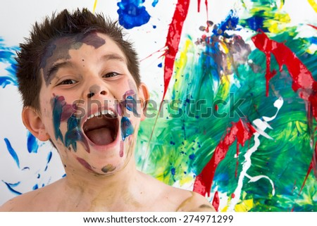 Funny artistic little boy with paint splodges on his face standing in front of his completed modern abstract creation laughing at the camera with his mouth wide open - stock photo