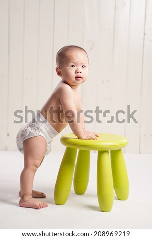 Funny asian baby standing up against a green chair - stock photo